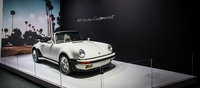 A classic Porsche 911 Turbo Cabriolet guards the entrance to the Porsche stand.